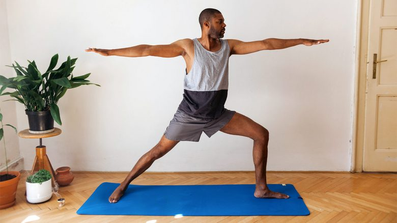 Adult man doing yoga at home